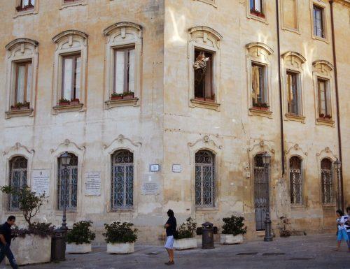 Stupore a Lecce, dal palazzo del Comune spunta una giraffa supina